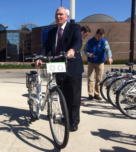 Fort Wayne Mayor Tom Henry stands with one of the city's new bicycles in its new bike-share program.