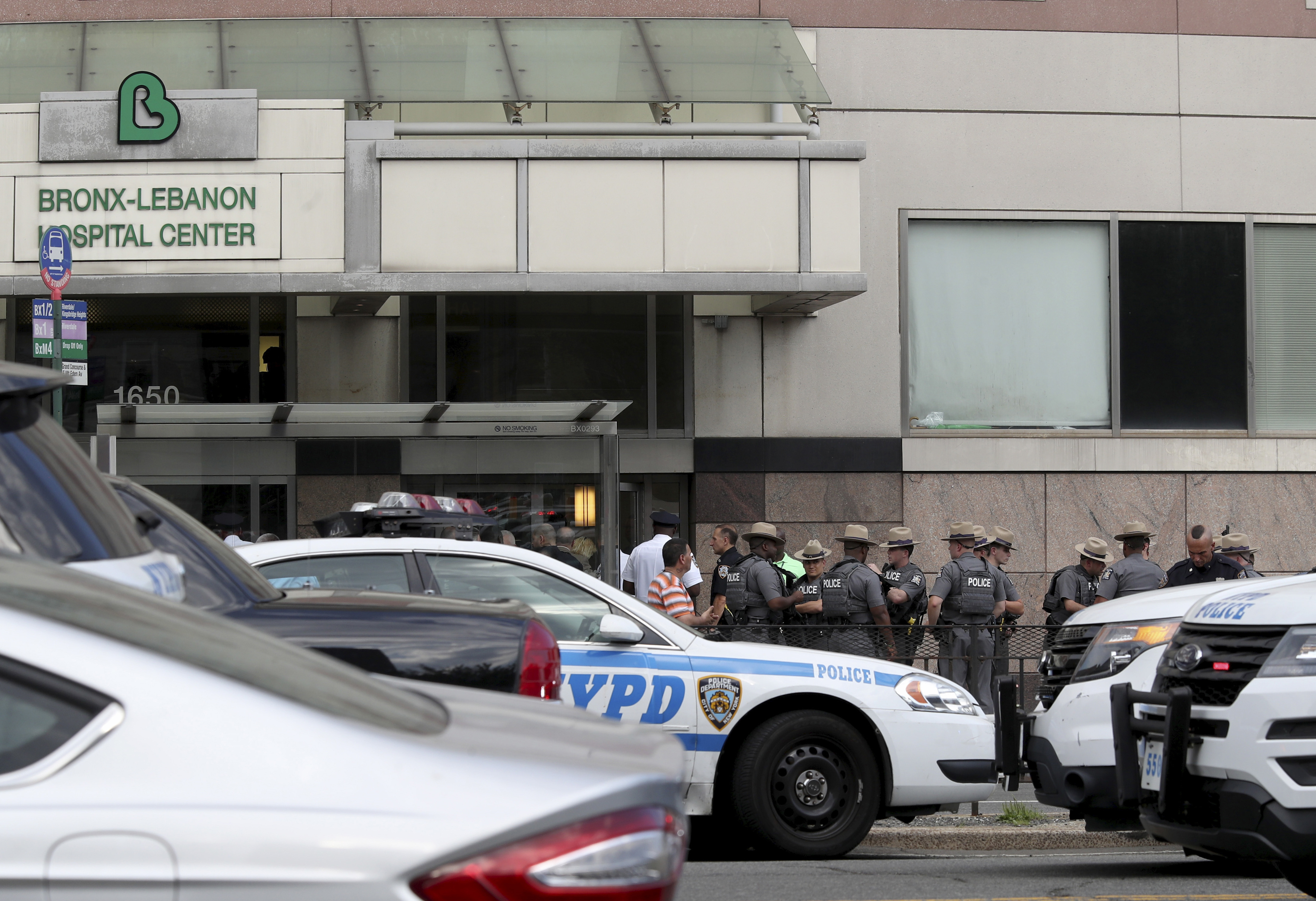 Police gather outside Bronx Lebanon Hospital in New York after a gunman opened fire and then took his own life there on Friday, June 30, 2017. (AP Photo/Mary Altaffer)