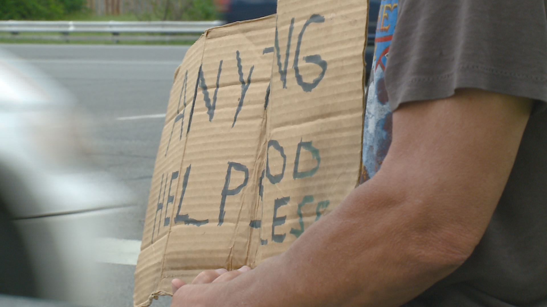 Man sits on side of street with sign asking for money fomr passing cars, a process called panhandling.